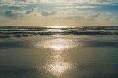 Sonnenbeschiene Wellen am Strand Stockfoto