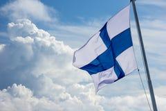 Sonnenbeschienes finnisches Flaggenfliegen im Wind stockbild