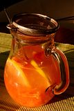 Sonnenbeschienes Glasgefäß mit frischem Orangensaft, Löffel und rostfreiem Sieb Stockfoto