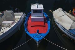Sonnenbeschienes Rot-, weißes und Blauesmittelmeerfischerboot auf Wasser in Euboea - Nea Artaki, Griechenland stockfoto