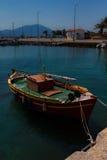Sonnenbeschienes rotes, gelbes, grünes und orange Mittelmeerfischerboot auf Wasser in Euboea - Nea Artaki, Griechenland stockbild
