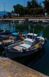 Sonnenbeschienes weißes Mittelmeerfischerboot mit der griechischen Flagge auf Wasser in Euboea - Nea Artaki, Griechenland lizenzfreie stockbilder