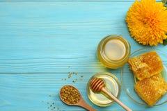 Sonnenblume mit Honig, Bienenwaben- und Honigschöpflöffel auf blauem Holztisch Draufsicht mit Kopienraum Stockfotos