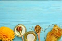 Sonnenblume mit Honig, Bienenwaben- und Honigschöpflöffel auf blauem Holztisch Draufsicht mit Kopienraum Lizenzfreie Stockbilder