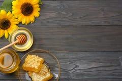 Sonnenblume mit Honig, Bienenwaben- und Honigschöpflöffel auf dunklem Holztisch Draufsicht mit Kopienraum Lizenzfreie Stockbilder