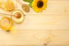 Sonnenblume mit Honig, Bienenwaben- und Honigschöpflöffel auf hellem Holztisch Draufsicht mit Kopienraum Lizenzfreies Stockbild