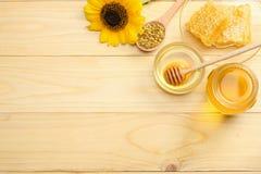 Sonnenblume mit Honig, Bienenwaben- und Honigschöpflöffel auf hellem Holztisch Draufsicht mit Kopienraum Lizenzfreie Stockfotografie