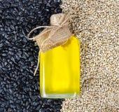 Sonnenblumenöl in einer in Handarbeit gemachten Glasflasche auf dem Hintergrund von Sonnenblumensamen stockfotos