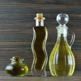 Sonnenblumenöl und Olivenöl in den Flaschen auf hölzernem Hintergrund Stockfoto
