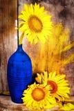 Sonnenblumen auf einem blauen Vase mit einem alten hölzernen Plankenhintergrund Lizenzfreies Stockfoto