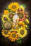 Sonnenblumen und Flasche Öl auf dunklem hölzernem Hintergrund lizenzfreie stockfotografie