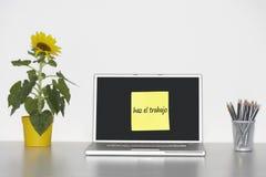 Sonnenblumenanlage auf Schreibtisch und klebriges Briefpapier mit spanischem Text auf dem Laptopschirm, der haz EL-trabajo sagt (e Stockfotografie