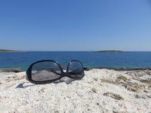 Sonnenbrille auf dem Felsen durch das Meer Lizenzfreies Stockfoto