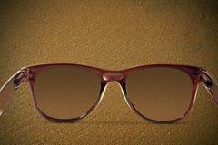 Sonnenbrille auf dem Sand Stockbild