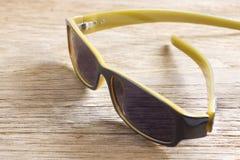 Sonnenbrille auf einer Holztischnahaufnahme Stockbild