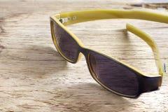 Sonnenbrille auf einer Holztischnahaufnahme Stockbilder