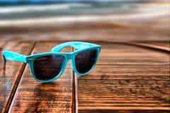 Sonnenbrille auf hölzernem Schreibtisch am Sommer Stockfotografie