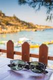 Sonnenbrille auf Holztisch mit Meer im Hintergrund Lizenzfreie Stockfotografie