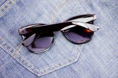 Sonnenbrille auf Jeans Stockfoto