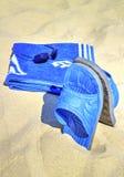Sonnenbrille, blaues Tuch und Pantoffel auf sandigem Strand Lizenzfreies Stockfoto