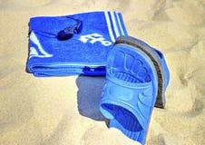 Sonnenbrille, blaues Tuch und Pantoffel auf sandigem Strand Lizenzfreie Stockfotos