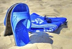 Sonnenbrille, blaues Tuch und Pantoffel auf sandigem Strand Stockfoto