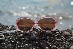 Sonnenbrille, die auf dem Strand liegt Lizenzfreies Stockfoto
