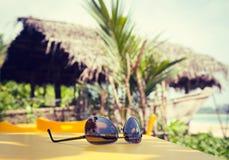 Sonnenbrille, die auf einer gelben Tabelle in einem tropischen Strandcafé liegt Lizenzfreies Stockfoto