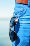 Sonnenbrille, die aus vorderer Tasche auf Blue Jeans heraus hängt lizenzfreie stockbilder