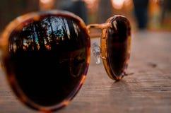 Sonnenbrille, die den Sonnenuntergang betrachtet lizenzfreies stockbild