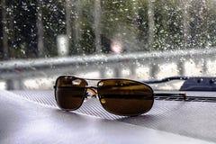 Sonnenbrille eines Kraftfahrers für einen hellen Sonnenschein, Lüge auf dem Torpedo eines Autos lizenzfreies stockbild