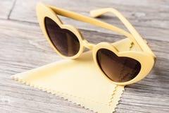Sonnenbrille in Form von Herzen und eine Serviette für das Abwischen von Gläsern auf einem hellen hölzernen Hintergrund Lizenzfreie Stockbilder