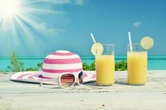 Sonnenbrille, Hut und Orangensaft Stockbilder