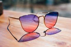 Sonnenbrille liegt auf dem Tisch stockbild