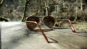 Sonnenbrille lokalisiert auf Tabelle in der Natur lizenzfreie stockfotografie