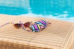 Sonnenbrille mit Badeanzug auf einem Sonnenruhesessel nahe Swimmingpool Stockbild
