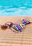 Sonnenbrille mit Badeanzug auf einem Sonnenruhesessel nahe Swimmingpool Lizenzfreie Stockbilder