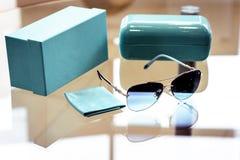 Sonnenbrille mit blauen Linsen in einem Metallrahmen im Verbindung mit einem blauen Kasten und einer blauen Abdeckung auf dem Gla lizenzfreies stockfoto