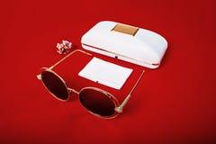 Sonnenbrille mit braunen Linsen auf einem roten Hintergrund stockfotografie