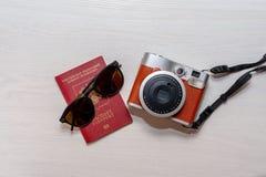 Sonnenbrille mit dem Pass eines Bürgers der Russischen Föderation und einer sofortigen Fotokamera auf einem weißen hölzernen Hint lizenzfreies stockbild