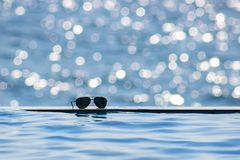 Sonnenbrille nahe dem Rand eines Swimmingpools Sommerkonzept mit Kopienraum Sonnenlicht bokeh stockbilder