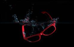 Sonnenbrille-Spritzen im Wasser Stockbild