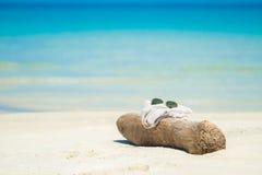 Sonnenbrille stellte auf einen hölzernen Stock auf dem Strand ein Meer und Ozean während des Sommers Stockfotos