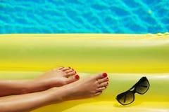 Sonnenbrille und aufblasbare matress Beine schlie?en oben Kreatives Gel lizenzfreies stockbild