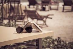 Sonnenbrille und Buch, die auf einer Tabelle in einem tropischen Strandcafé liegen Lizenzfreie Stockfotos