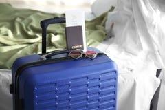 Sonnenbrille und Dokumente auf Reisekoffer zuhause stockbild