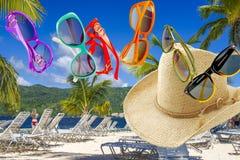 Sonnenbrille und ein Strohhut auf einem tropischen Landschaftshintergrund lizenzfreie stockfotos