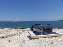 Sonnenbrille und Handy auf dem Felsen durch das Meer Lizenzfreies Stockbild
