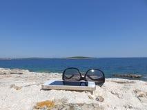 Sonnenbrille und Handy auf dem Felsen durch das Meer Stockfotografie