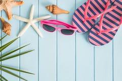 Sonnenbrille und Sandalen auf dem Bretterboden, Sommerkonzept Stockfoto